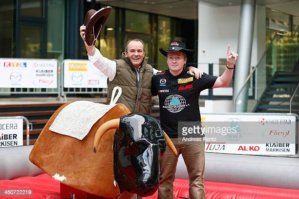 Moderator Wolfram Kons and Joey Kelly pose on a bull riding machine during a photocall on November 20 2013 in Cologne Germany Joey Kelly will go...