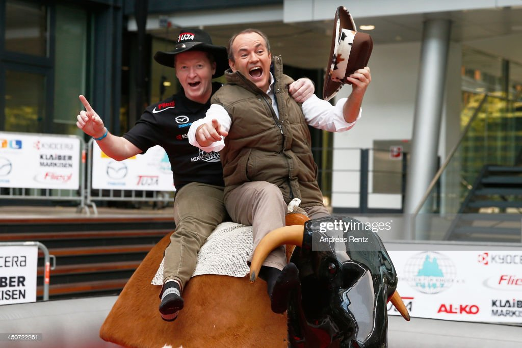 Moderator Wolfram Kons (R) and Joey Kelly (L) pose on a bull riding machine during a photocall on November 20, 2013 in Cologne, Germany. Joey Kelly will go riding 24 hours non stop during the RTL Spenden Marathon on November 22.