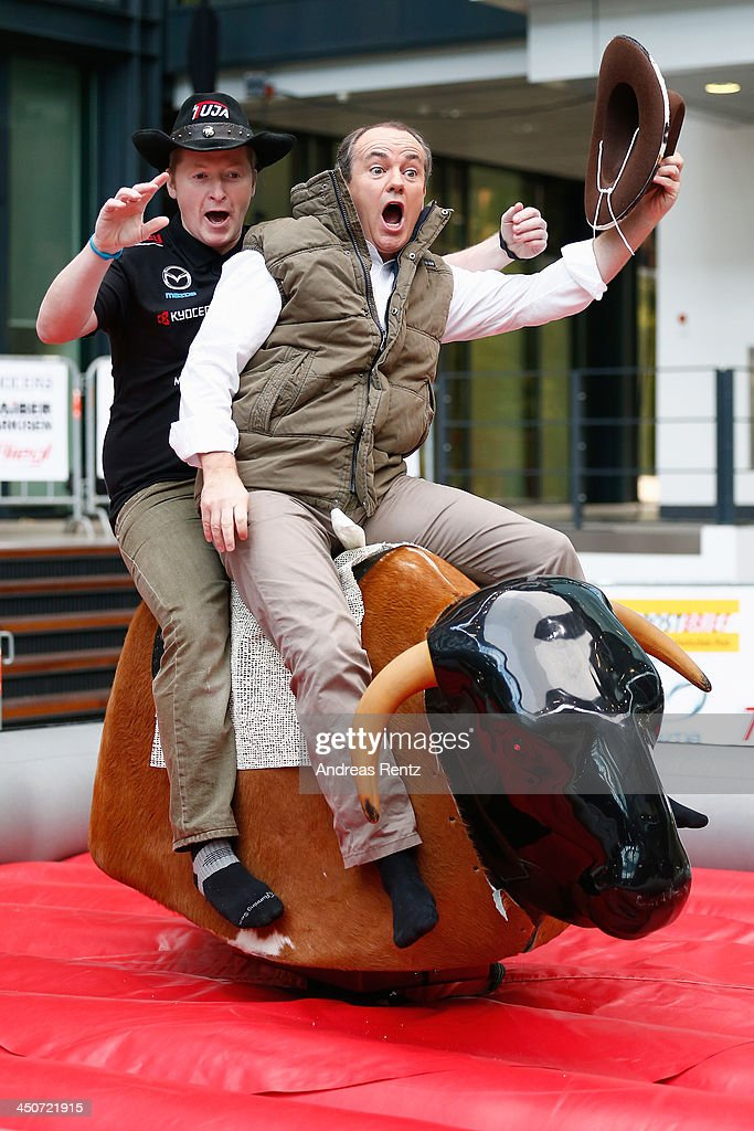 Moderator Wolfram Kons (R) and Joey Kelly (L) ride on a bull riding machine during a photocall on November 20, 2013 in Cologne, Germany. Joey Kelly will go riding 24 hours non stop during the RTL Spenden Marathon on November 22.