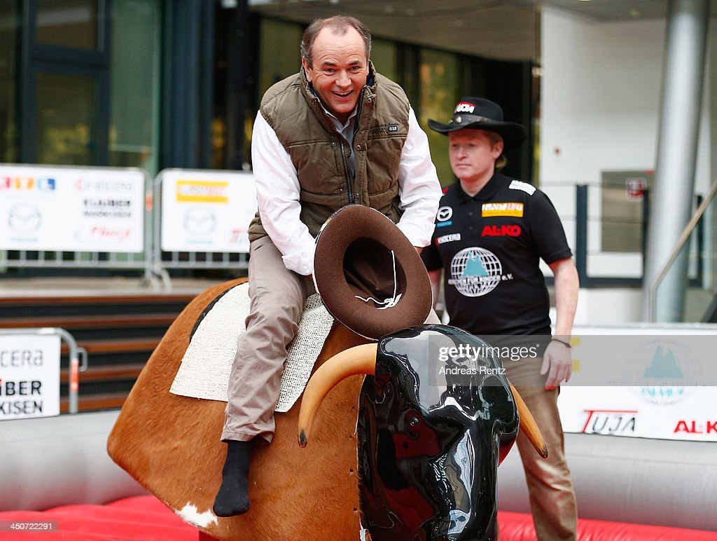 Moderator Wolfram Kons (L) poses on a bull riding machine during a photocall on November 20, 2013 in Cologne, Germany. Joey Kelly (R) will go riding 24 hours non stop during the RTL Spenden Marathon on November 22.