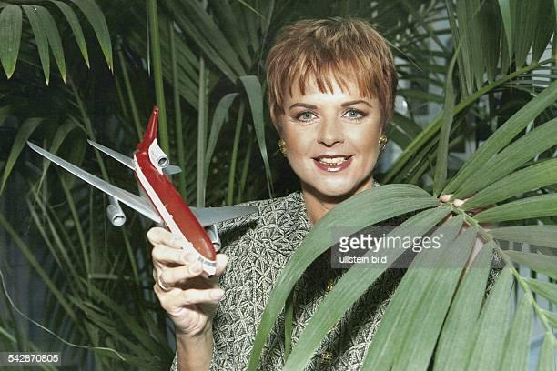 Moderatorin Alida Gundlach steht zwischen Palmen mit einem Flugzeugmodell in der Hand Undatiertes Foto