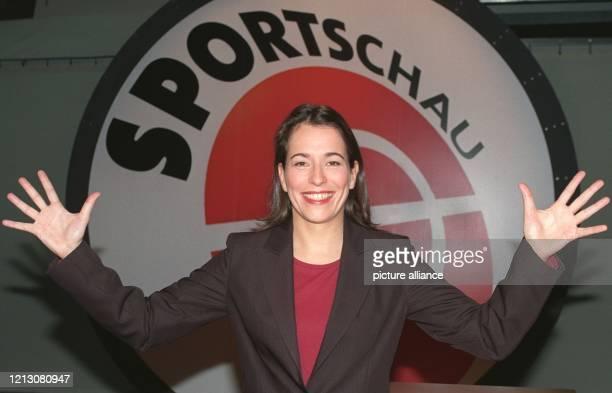 """Moderatorin Anne Will steht am im ARD-Studio in Köln mit ausgebreiteten Armen und einem strahlenden Lachen vor dem Logo der """"ARD-Sportschau"""". Anne..."""