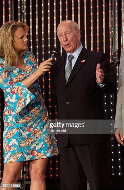 Moderatorin Barbara Schöneberger und der englische Fußballstar Sir Bobby Charlton anlässlich der Eröffnung der FIFA Fanmeile vor dem Brandenburger...