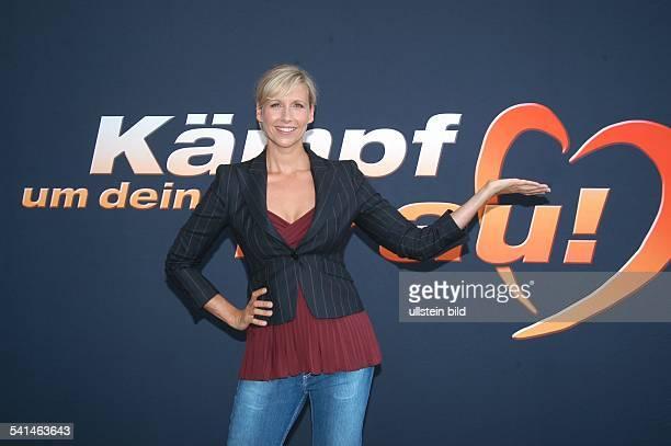 Moderatorin Dsteht vor dem Logo der Fernsehsendung 'Kämpf um deine Frau' von SAT1