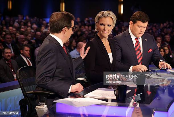 Moderators Chris Wallace pats on the shoulder of Megyn Kelly as they wait with Bret Baier for the beginning of the Fox News - Google GOP Debate...