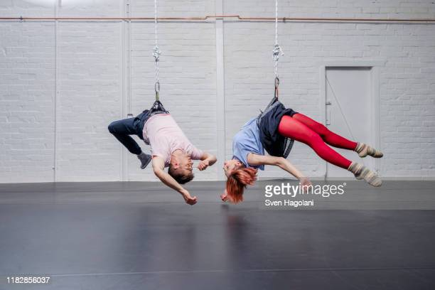 modern aerialist dancers performing, hanging upside-down - 空中曲芸師 ストックフォトと画像