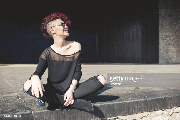 Modern and attractive girl with red hair sitting on the edge on an empty stage and enjoys in beautiful day outdoor.