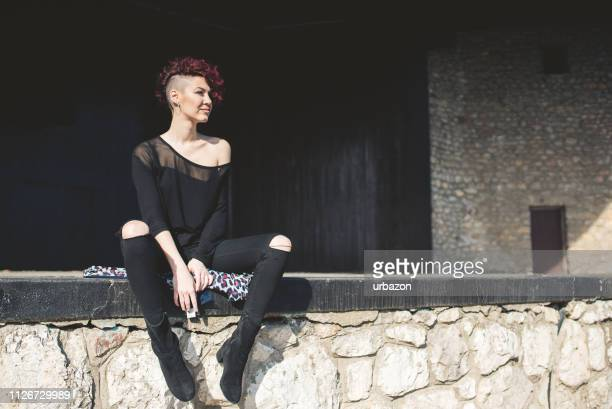 modern and attractive girl with red hair sitting on the edge on an empty stage and enjoys in beautiful day outdoor. - off shoulder stock pictures, royalty-free photos & images
