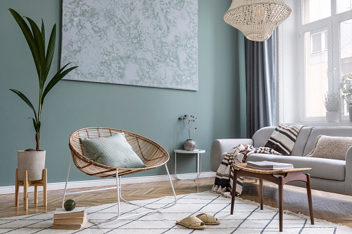 Modern and bohemian composition of interior design with gray sofa, rattan armchair, retro footrest, plaid, pillow, tropical plants, small table and elegant accessories. Stylish home decor. Template. 1166445580