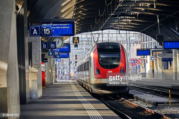 Modern and new Zurich Central Station with red and white Swiss train leaving the platform