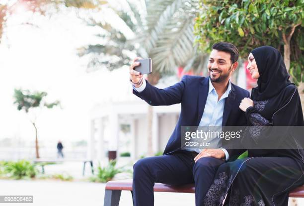 Modern Arab couple using a smart phone to take a selfie to post on social media