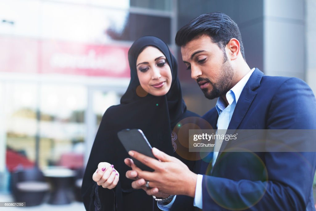 Modern Arab husband showing his wife an online message on his smart phone : Stock Photo