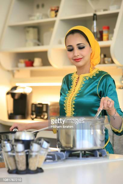 modern arab moroccan woman cooking in kitchen in her house. - moroccan culture stock photos and pictures