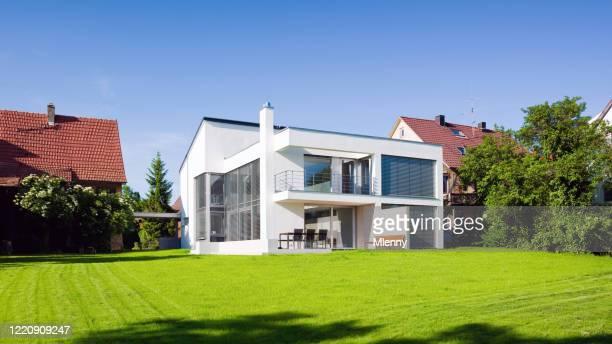 moderne architektur haus grün auf grüner sommerwiese - immobilie stock-fotos und bilder