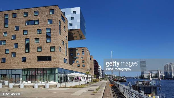 modern architecture of nh hotel along the riverbank of spree river in the district of friedrichshain, berlin, germany - spree river stock pictures, royalty-free photos & images