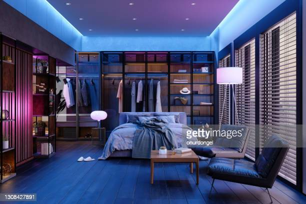 modern bedroom interior at night with neon light. messy bed, clothes in closet, armchairs and floor lamp. - ambient light stock pictures, royalty-free photos & images