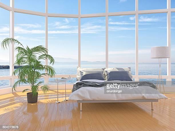 Moderne Schlafzimmer-Interieur mit Fenster über Wolkengebilde das Meer