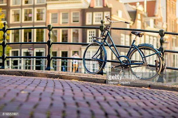 modern bicycle parked against canal bridge - image stock pictures, royalty-free photos & images