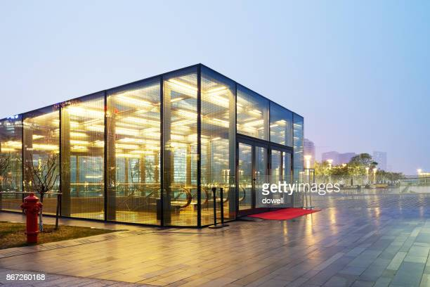 modern building with glass wall on square at twilight