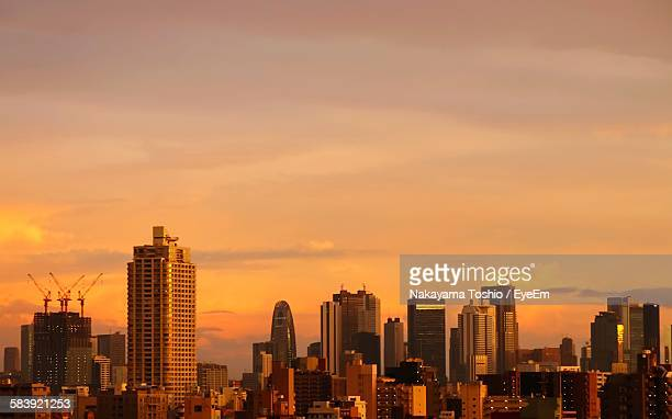 modern buildings against sky during sunset - 夕暮れ ストックフォトと画像