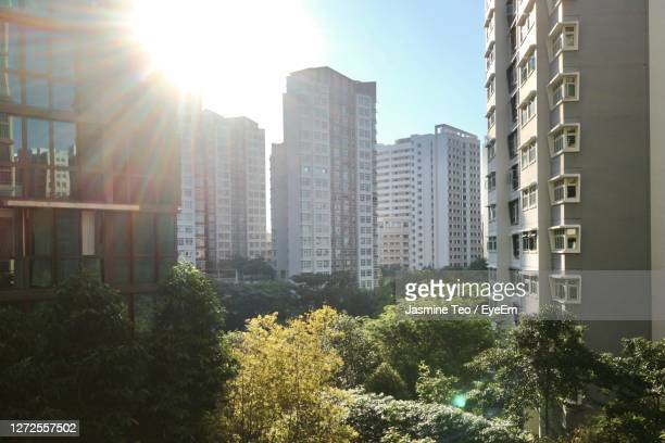 modern buildings against sky on sunny day - singapore stock pictures, royalty-free photos & images