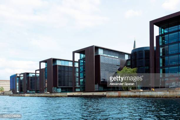 modern buildings along the canal in christianshavn district in copenhagen, denmark - uferviertel stock-fotos und bilder
