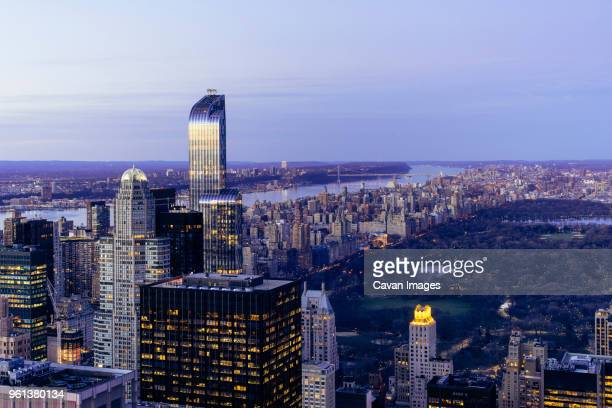 modern buildings by central park against sky at dusk - central park reservoir stock pictures, royalty-free photos & images