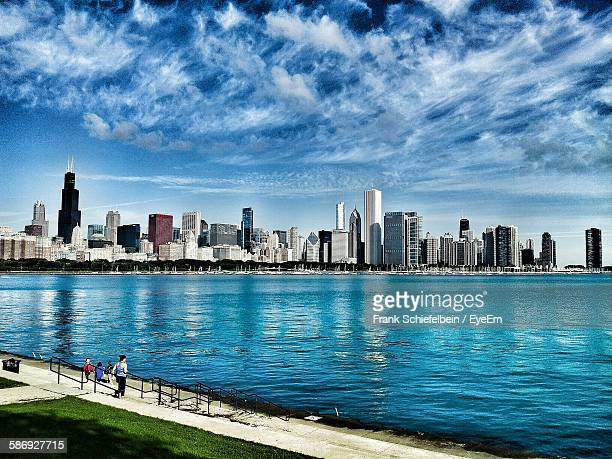 Modern Buildings By Lake Michigan Against Cloudy Sky