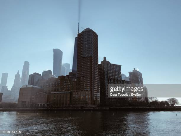 modern buildings by river against clear blue sky in city - data topuria stock pictures, royalty-free photos & images