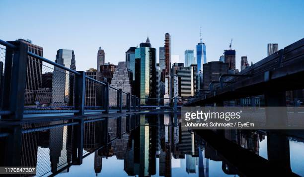 modern buildings by river against clear sky - building story stock pictures, royalty-free photos & images