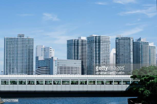 modern buildings by river against sky in city - 神奈川県 ストックフォトと画像