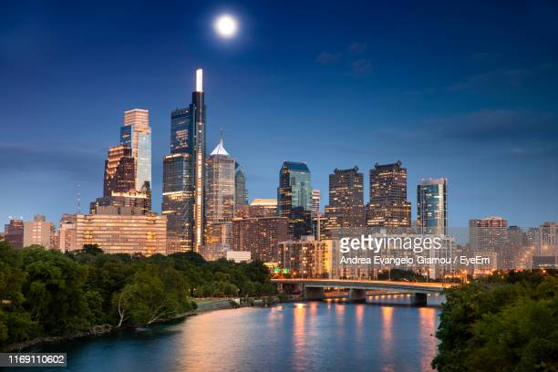 modern buildings by river against sky in city - philadelphia skyline stock pictures, royalty-free photos & images