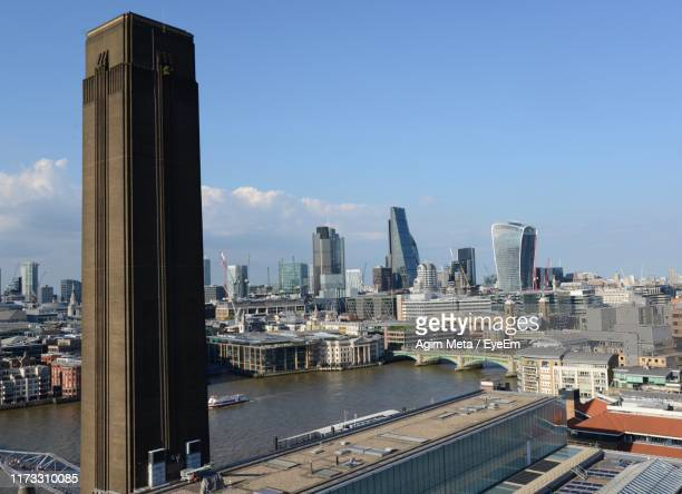 modern buildings by river against sky in city - agim meta stock pictures, royalty-free photos & images