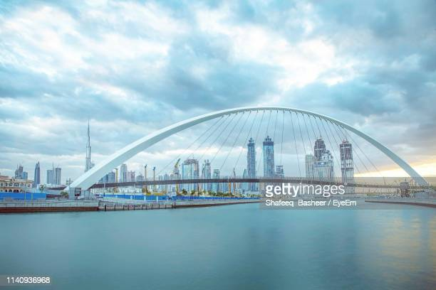 modern buildings by river in city against cloudy sky - overcast stock pictures, royalty-free photos & images