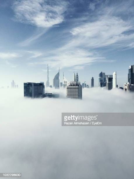 modern buildings covered with clouds in city - wolkenkratzer stock-fotos und bilder