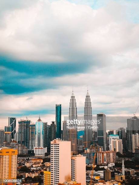modern buildings in city against cloudy sky - hakimi stock photos and pictures