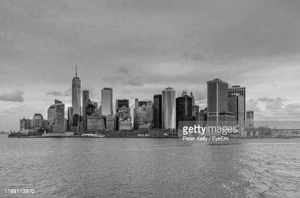 modern buildings in city against cloudy sky - staten island ferry stock pictures, royalty-free photos & images