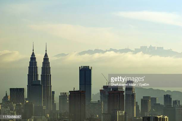 modern buildings in city against cloudy sky - shaifulzamri eyeem stock pictures, royalty-free photos & images