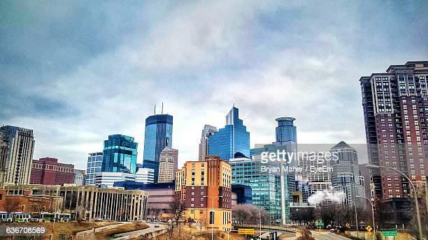 modern buildings in city against cloudy sky - minneapolis stock pictures, royalty-free photos & images