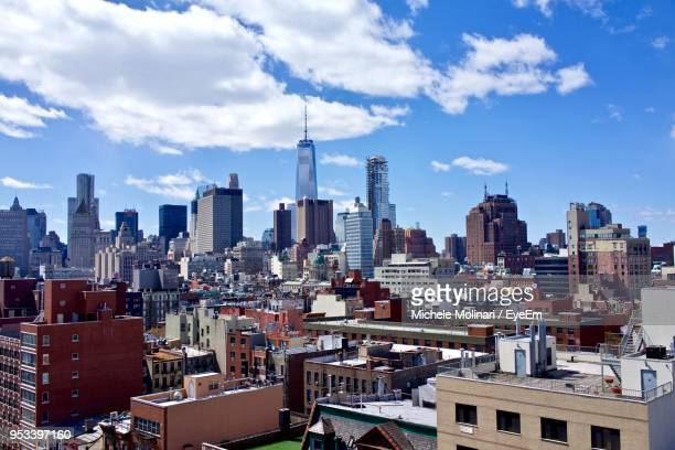 modern buildings in city against cloudy sky - lower east side manhattan stock pictures, royalty-free photos & images