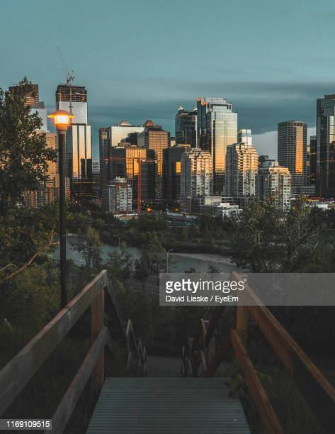 modern buildings in city against sky at dusk - calgary stock pictures, royalty-free photos & images