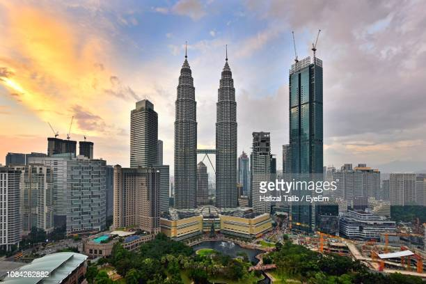 modern buildings in city against sky during sunset - menara kuala lumpur tower stock photos and pictures