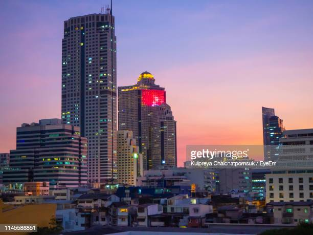 modern buildings in city against sky during sunset - thai mueang photos et images de collection