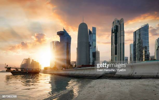 modern buildings in city against sky during sunset - doha stockfoto's en -beelden