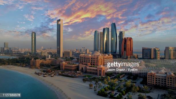 modern buildings in city against sky - abu dhabi stock pictures, royalty-free photos & images