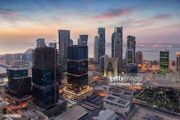 modern buildings in city by river against sky during sunset - qatar stock pictures, royalty-free photos & images