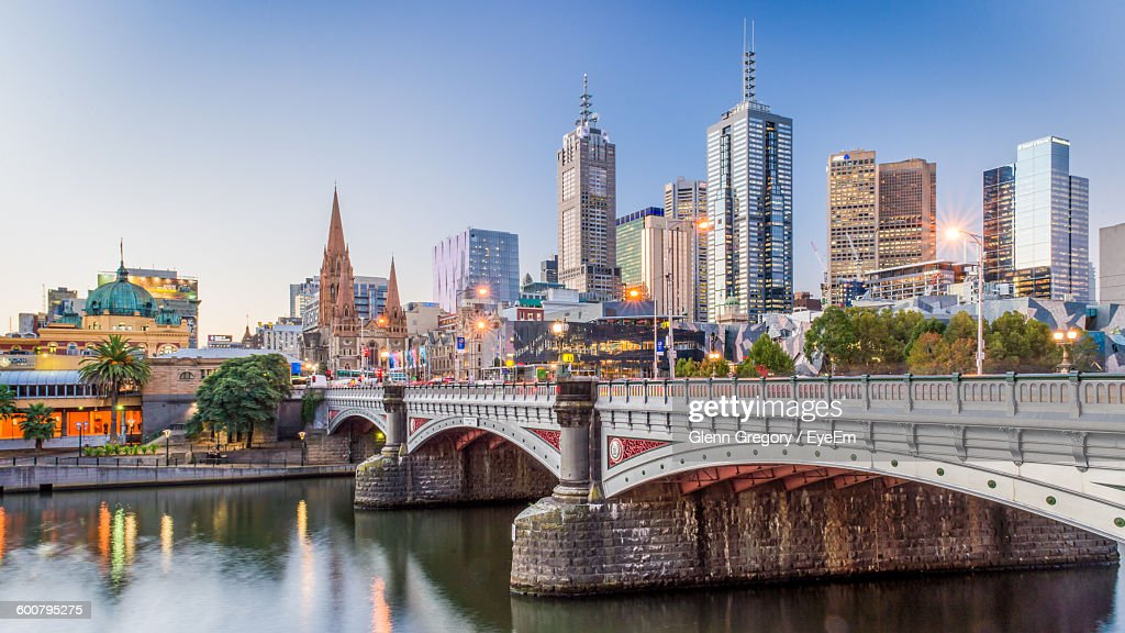 Modern Buildings In Front Of Yarra River Against Clear Sky At Dusk : Stock Photo