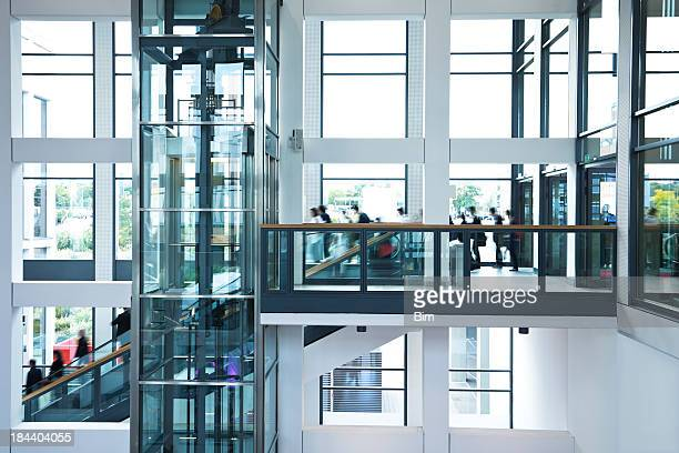 Modern Business Hall with Blurred People, Stairs, Escalators and Elevator