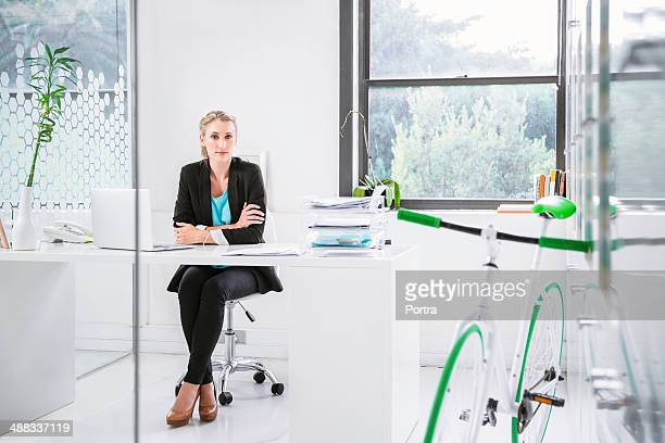 Modern business woman with a bike in her office