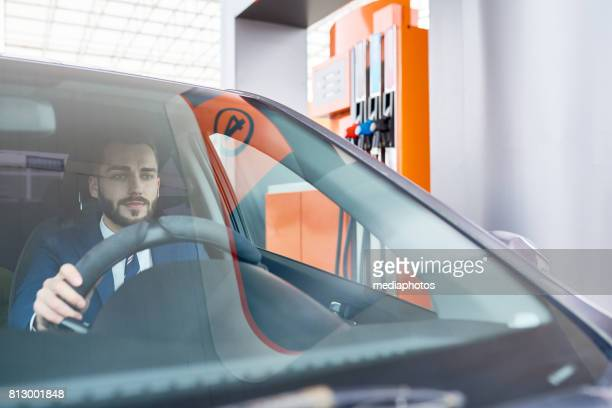 Modern Businessman in Car at Gas Station